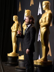 Casey Affleck poses in the press room with the Oscar