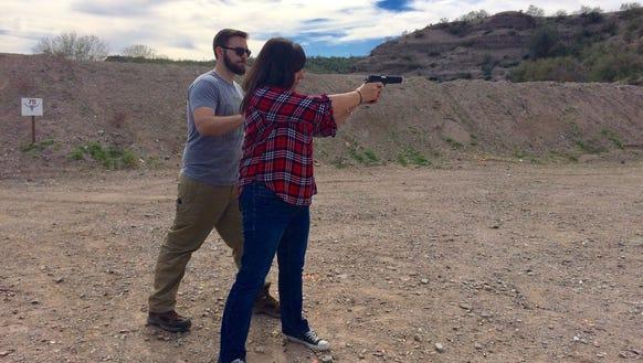Virgil Bland instructs Karina Bland in firing a pistol