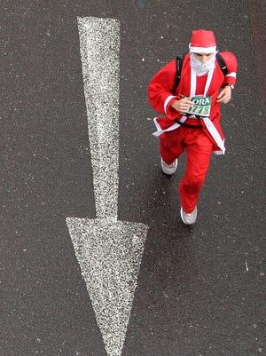 Man dressed as Santa Claus goes for a run.