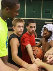 (Left to right) Brad Reese, Tyler Simmons, Christian Livengood and Patrick Cassel huddle up with other participants after practice for the Brad Reese San Angelo Area Basketball Camp in 2013.