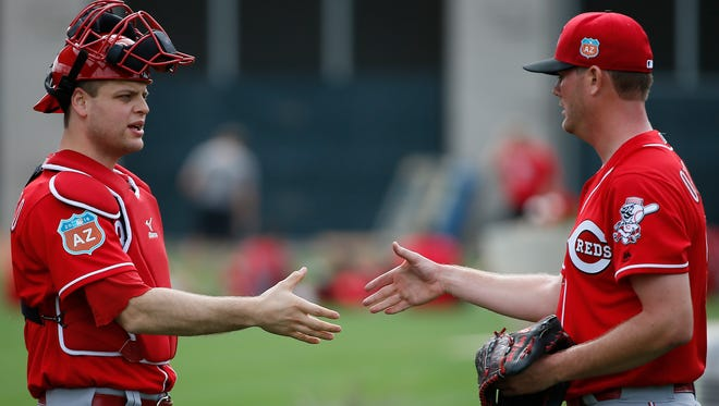 Cincinnati Reds catcher Devin Mesoraco (39), left, shakes hands with pitcher Chris O'Grady (56), right, after a bullpen session during Cincinnati Reds spring training, Thursday, Feb. 18, 2016, in Goodyear, Arizona.