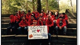 Daniel Marcus (seen holding the sign) hopes to win $30,000 for a cafeteria makeover for Sacred Heart School in Camden,