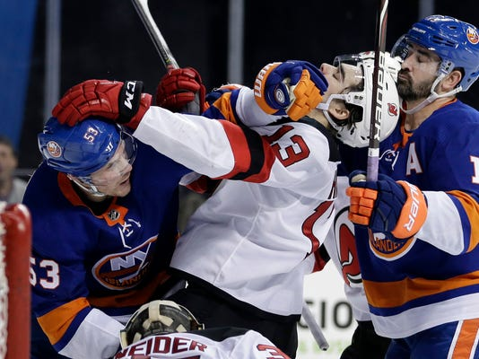 New York Islanders' Casey Cizikas, left, and Cal Clutterbuck, right, scuffle with New Jersey Devils' Nico Hischier, center, during the second period of an NHL hockey game, Sunday, Jan. 7, 2018, in New York. (AP Photo/Seth Wenig)