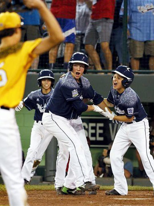 Adam Cramer, right, and Cole Wagner, center, celebrate after Red Land's dramatic 9-8 win over South Carolina on Sunday night at the Little League World Series in South Williamsport.