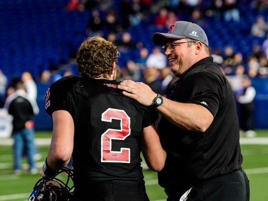Southridge's Jayce Harter (2) and Head Coach Scott Buening walk across the field as Harter is named the Mental Attitude Award winner after the IHSAA Class 2A State Championship game at Lucas Oil Stadium in Indianapolis, Ind., Saturday, Nov. 25, 2017. Harter won an $1,000 scholarship for his school.