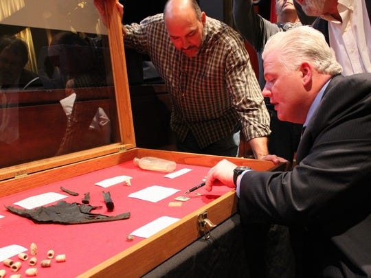 Historian John Marler shows some of the 900 artifacts he excavated from the cellar of the Lotz House.