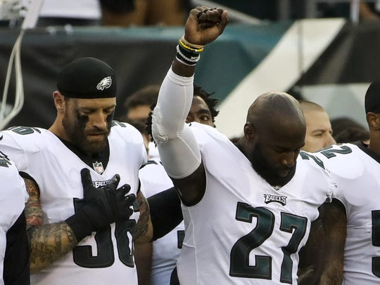 The Eagles' Chris Long (56) stands beside Malcolm Jenkins