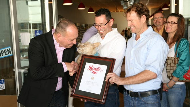 Indio Mayor Glenn Miller greets Jack Farley at the opening of owners James Mancini and Michael Heath's fourth art store.