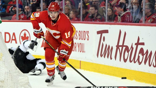 Calgary Flames forward Matthew Tkachuk (19) chases after the puck after a collision with Los Angeles Kings defenseman Drew Doughty during the first period.