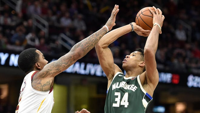 Giannis Antetokounmpo goes up for a shot as Cleveland Cavaliers guard JR Smith defends in the third quarter.
