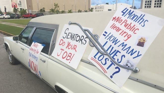 A Cadillac hearse sits parked in front of the Guam Congress Building Friday morning, covered with signs encouraging lawmakers to move forward with the governor's plan to borrow money to modernize Guam Memorial Hospital.