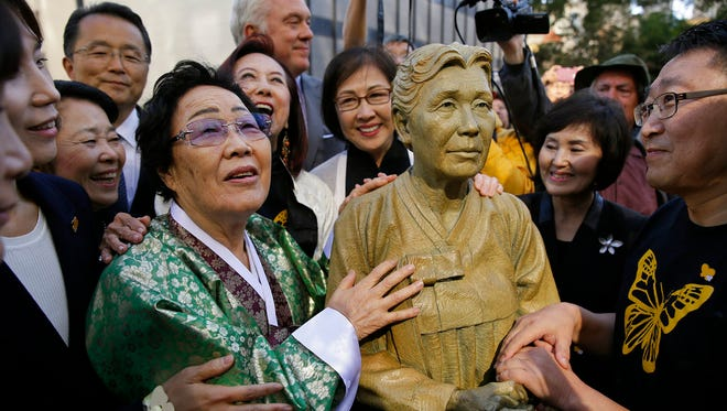"""In this Friday, Sept. 22, 2017, file photo, former World War II """"comfort woman"""" Yongsoo Lee, 89, of South Korea, stands by a statue of Haksoon Kim while looking at the """"Comfort Women"""" monument after it was unveiled in San Francisco. Japan has expressed strong regret over San Francisco's decision to give formal city property status to a statue commemorating women who worked in military-backed brothels for Japanese troops during World War II, with Osaka declaring it will terminate its 60-year sister-city ties."""