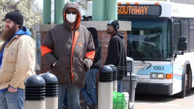 People wait for buses at the SARTA Cornerstone Transit Center in Canton on Wednesday, April 15, 2020. Because of the coronavirus pandemic, masks are required on all buses.