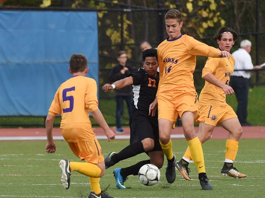 Rhinebeck's Lex Kronbichler, right, and Dover's Ramiro Geronimo, center, fight for the ball during Thursday's Class B boys soccer final at Middletown High School.