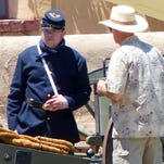 A volunteers wearing the soldier's uniform of the fort era discusses the mechanisms of a cannon with a visitor to the annual Fort Stanton Live event. Historic sites in Lincoln County depend on the support and participation of volunteers.