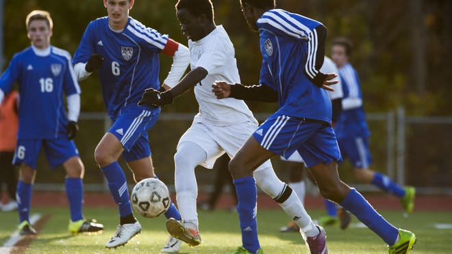 Burlington's Seraphin Iradukunda (11) gets past Mount Anthony's Jack Peterson (6) and Mount Anthony's Ben Winslow (7) with the ball during the quarterfinal boys soccer game between Mount Anthony and Burlington at Buck Hard Field in 2015.