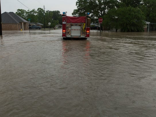 A firetruck makes its way down a flooded Carencro street