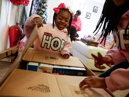 Ke'ani, left, and Shania Page open Christmas gifts