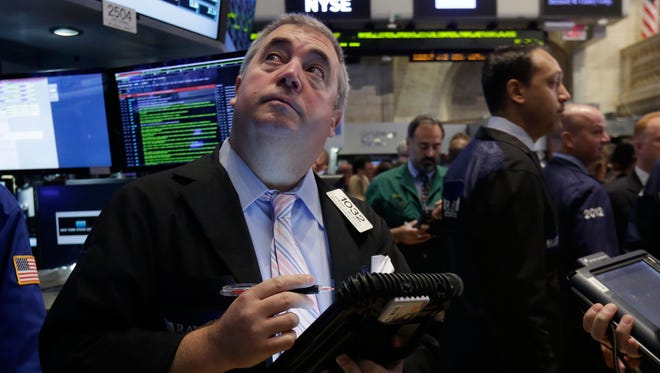 In this Thursday, Aug. 21, 2014, file photo, trader Edward McCarthy, left, works on the floor of the New York Stock Exchange.