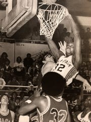 Edgar Jones dunks over Santa Clara's Kurt Rambis during a 1977 game in the Virginia Street Gym.