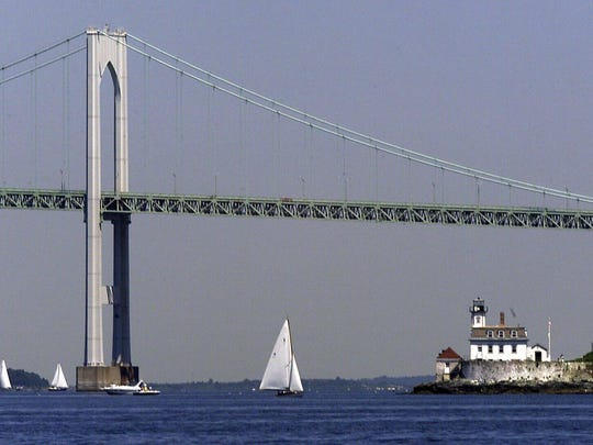 The Newport Bridge spanning the Narragansett Bay between Jamestown and Newport, R.I., towers over sailboats and the Rose Island lighthouse, right, in this July 31, 2001, file photo.