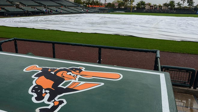 The field is covered with a tarp as rain comes down at Ed Smith Stadium in March.