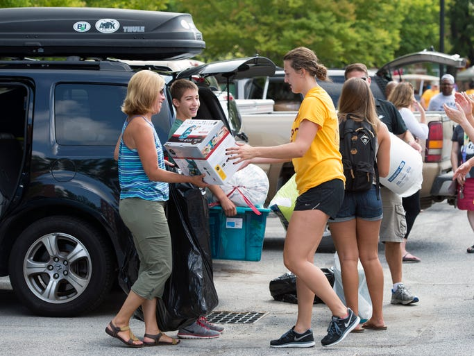 "Members of the Salisbury University Volleyball team help freshmen move into their dorms Thursday. A crowd of students clad in yellow ""Need Help?"" shirts greeted new students and parents in parking lots to unload and carry luggage."