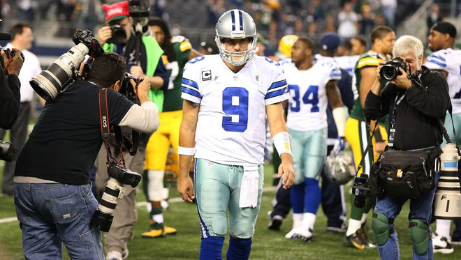 Dallas Cowboys quarterback Tony Romo (9) walks off the field as photographers capture images after the game against the Green Bay Packers at AT&T Stadium.