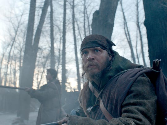 "Tom Hardy (foreground) and Will Poulter hunt for the person they had left for dead, in .""The Revenant."""