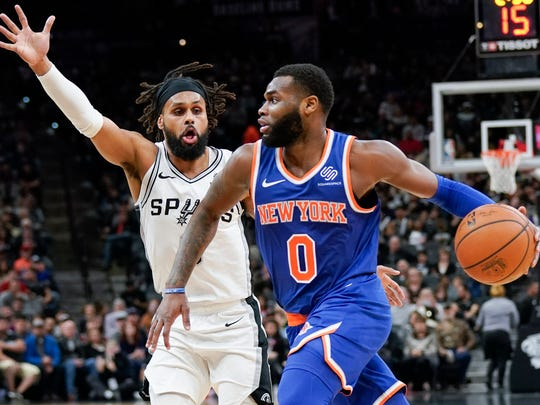 New York Knicks' Kadeem Allen (0) drives against San Antonio Spurs' Patty Mills during the first half of an NBA basketball game Friday, March 15, 2019, in San Antonio. (AP Photo/Darren Abate)