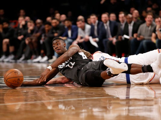 Brooklyn Nets guard Caris LeVert (22) loses the ball after colliding with New York Knicks guard Ron Baker. left, in the fourth quarter of an NBA basketball game, Thursday, Dec. 14, 2017, in New York. New York Knicks guard Courtney Lee recovered the turnover and hit a three-pointer to lift the Knicks to a significant lead as the Knicks defeated the Nets 111-104. (AP Photo/Kathy Willens)