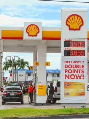 A drop of 10-cents per gallon for gasoline is reflected on a sign as vehicles are refueled at the Shell gas station on Chalan San Antonio in Tamuning on Wednesday, July 27.