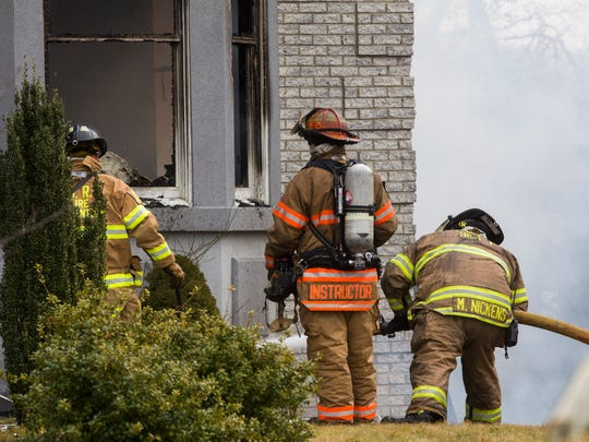 Fireman work to extinguish house fire at 1911 Fiddlers