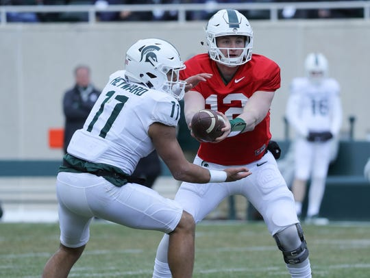Michigan State quarterback Rocky Lombardi hands off to running back Connor Heyward during the 2018 spring game April 7 at Spartan Stadium.
