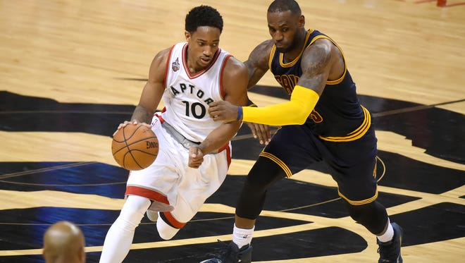 Toronto Raptors guard DeMar DeRozan (10) dribbles the ball past Cleveland Cavaliers forward LeBron James (23) in game three of the Eastern conference finals of the NBA Playoffs at Air Canada Centre.