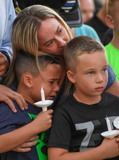 A family grieves during a candlelight vigil for Charleston Hartfield at Police Memorial Park. Hartfield, an off-duty Las Vegas police officer was killed Sunday during the mass shooting at a music festival across from the Mandalay Bay Hotel and Casino.