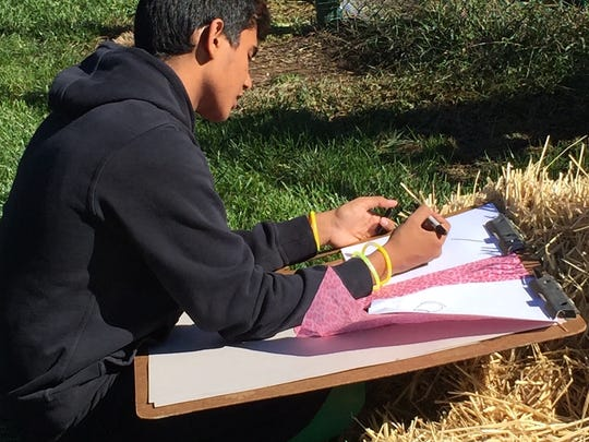 Art In the Outdoors... Zishan Sajid of Carteret, a senior at The Wardlaw-Hartridge School in Edison, spends some time line drawing in the school's new garden. The drawings were executed on tissue paper to be used next month in a surface treatment project with a garden drawing overlay.