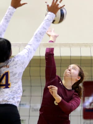 Licking Heights senior Natalie Satterwhite attempts to tip the ball over the Reynoldsburg front line this past Saturday during the Licking County Preview.