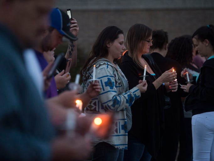 Attendees light candles to remember those who have