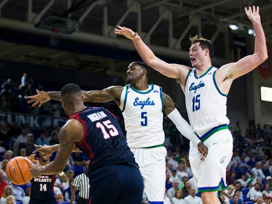 FGCU guard Zach Johnson (5) and forward Ricky Doyle (15) attempt to block a pass during a full court press against FAU at Alico Arena on Tuesday in the Eagles' 92-88 loss.