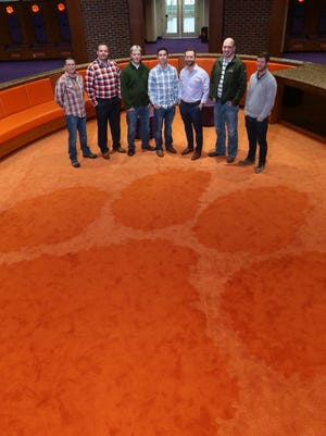 Harris Flooring America in Anderson employees stand by the tiger paw on Friday, inside the Clemson Football Facility's locker room in Clemson. The business placed the carpet in the newly opened 142,000-square-foot building, including wood tile in Dabo Swinney's office. From left: Dennis Owens, Mike Garren, James Lister, Russell Junkins, Scott Junkins, Drew Anderson, and Iain Mackay.