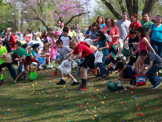 Children run into a field to pick up Easter eggs during an Easter egg hunt at Evangel Temple on Saturday, April 19, 2014.