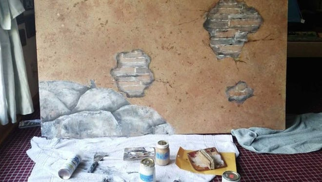 A portion of the painted creche for St. Teresa of Calcutta shows brick peaking through the stone plaster wall.