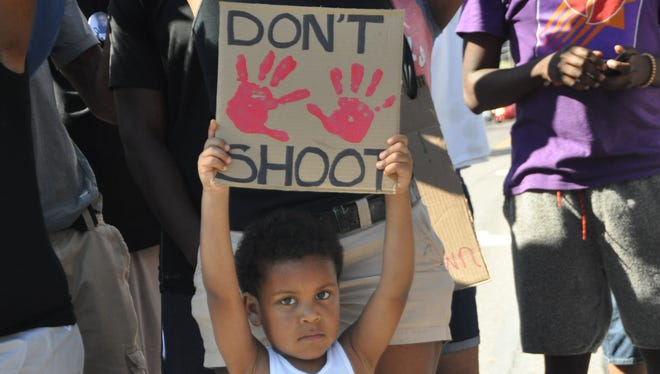 A boy holds up a sign during a peaceful pretest in Ferguson, Missouri, Wednesday afternoon.