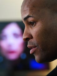 """Surgeon General Jerome Adams visits the National Safety Council's """"Prescribed to Death"""" Memorial as a screen beside him shows a video with Felicia Miceli of Illinois. Her son passed away from an overdose after an addiction to pain pills that started with a valid prescription following a football injury."""