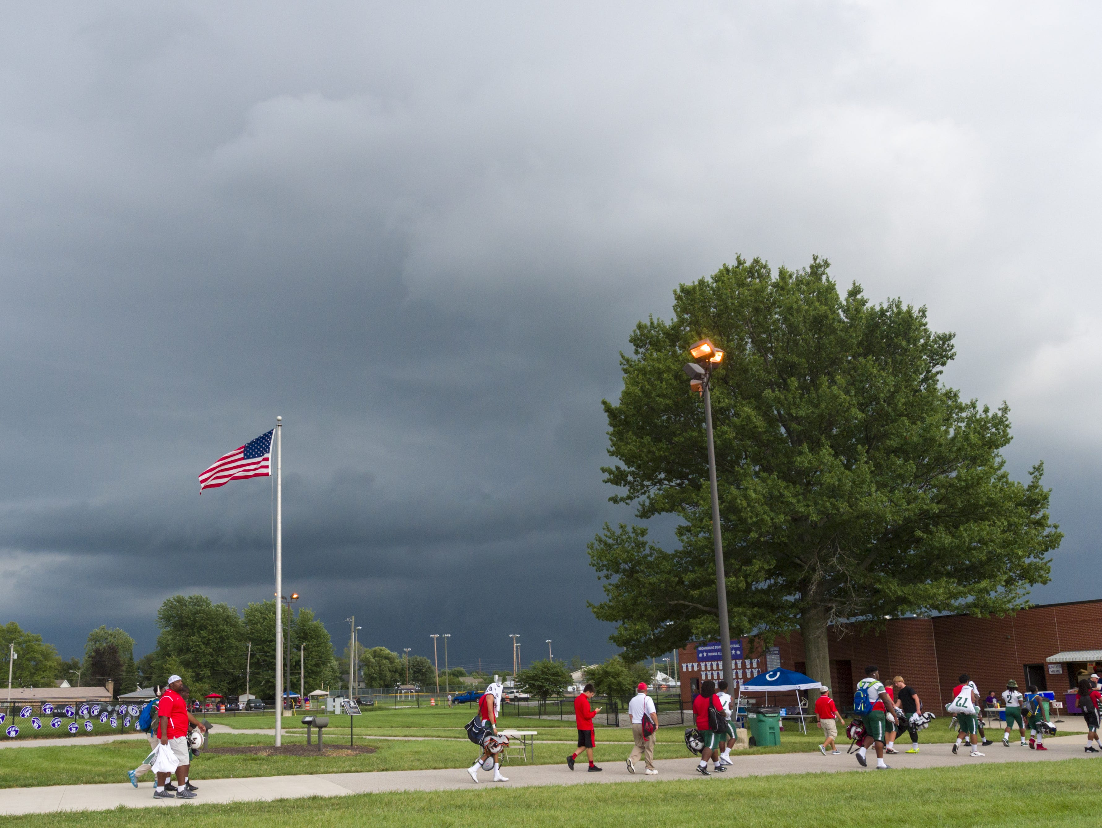 Lawrence North High School players head to safety inside Brownsburg High School as the game remains under a delay due to lightning. Brownsburg hosted Lawrence North in varsity football action Friday, August 26, 2016.