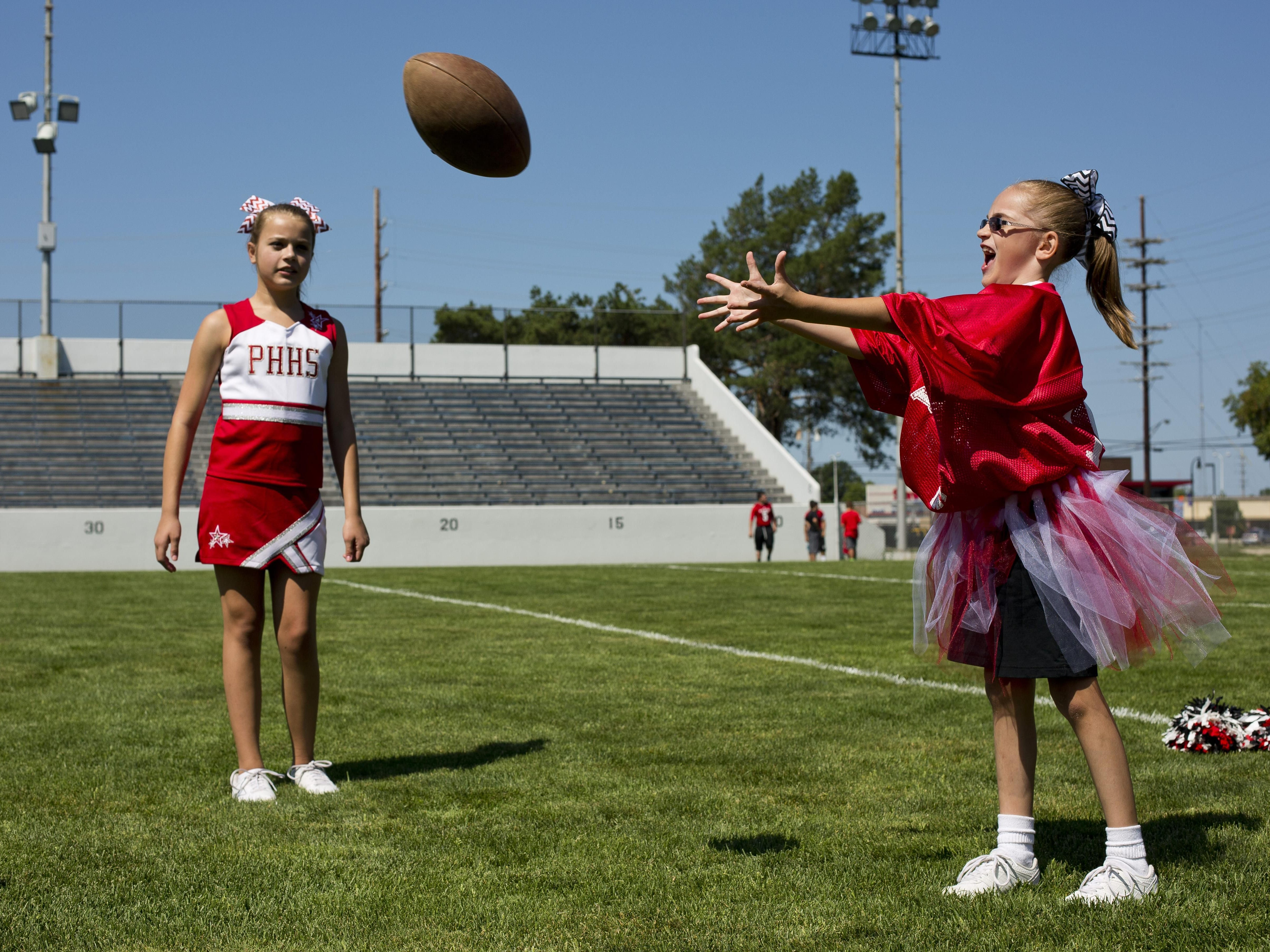 Gracie Allen, right, plays catch with mentor Victoria Johnson and others during Victory Day Saturday, August 15, 2015 in Memorial Stadium at Port Huron High School. The event paired special needs students with mentors from the football and cheerleading teams.