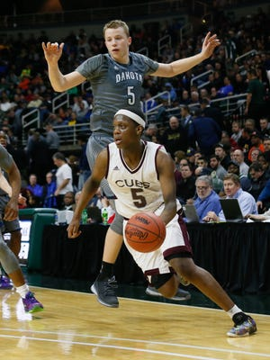 U-D Jesuit's Cassius Winston (5) dribbles past Macomb Dakota's Thomas Kithier during an MHSAA boys basketball Class A semifinal Friday, March 25, 2016, at the Breslin Center in East Lansing. U-D won, 72-51.