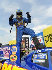 Funny Car driver Ron Capps celebrates on top of his car after winning the Summit Racing Equipment Nationals on June 26, 2016