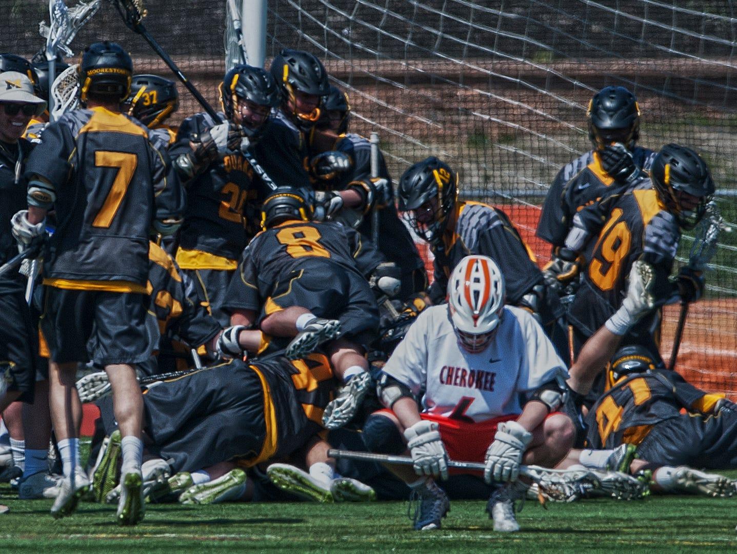 Cherokee's Jordan Krug looks dejected as Moorestown lacrosse players celebrate after winning in a double overtime against Cherokee at Cherokee High School